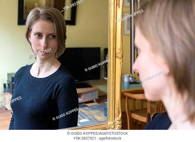 Tilburg, Netherlands. Young adult caucasian woman watching her reflection inside a living room mirror after doing her make up