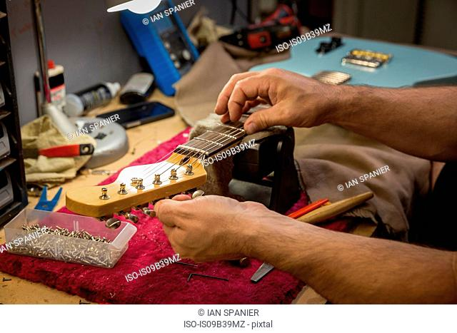 Cropped view of guitar maker's hands manufacturing guitar