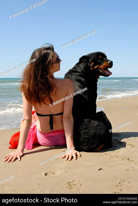 woman on the beach withe her rottweiler
