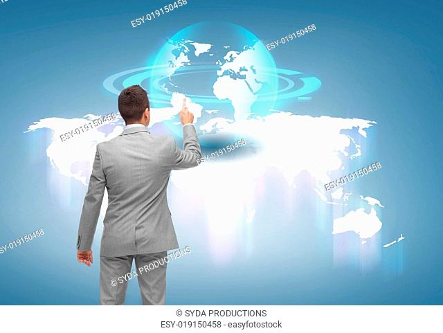 business, people and technology concept - businessman pointing finger or touching virtual globe projection over blue background from back
