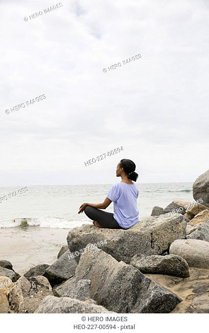 Serene woman sitting in lotus position beach rocks