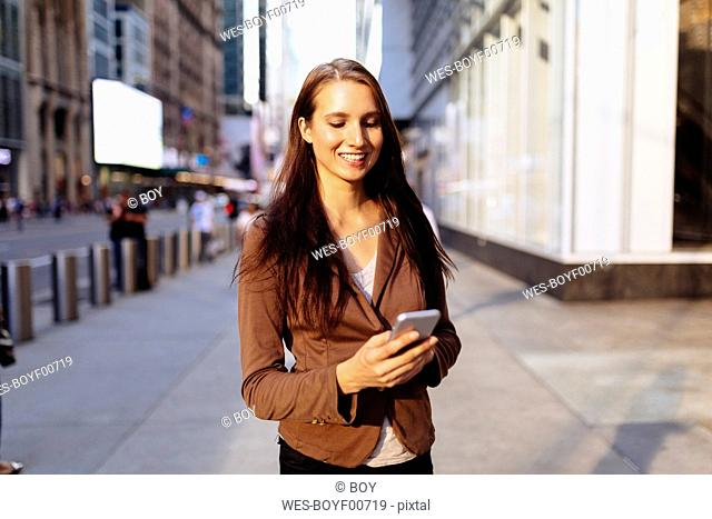 USA, New York, Manhattan, smiling young businesswoman looking at cell phone