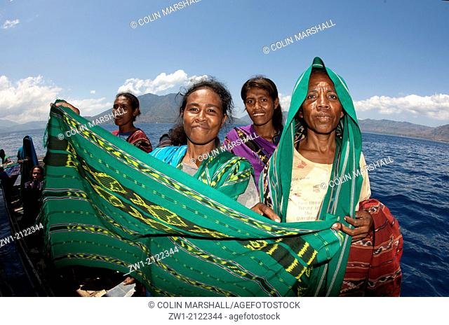 Women selling blankets (ikat) with volcano in background near Pura Island near Alor in eastern Indonesia