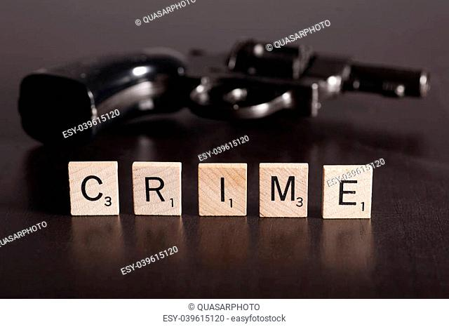 scrabble letters spelling the word crime with a gun in the background