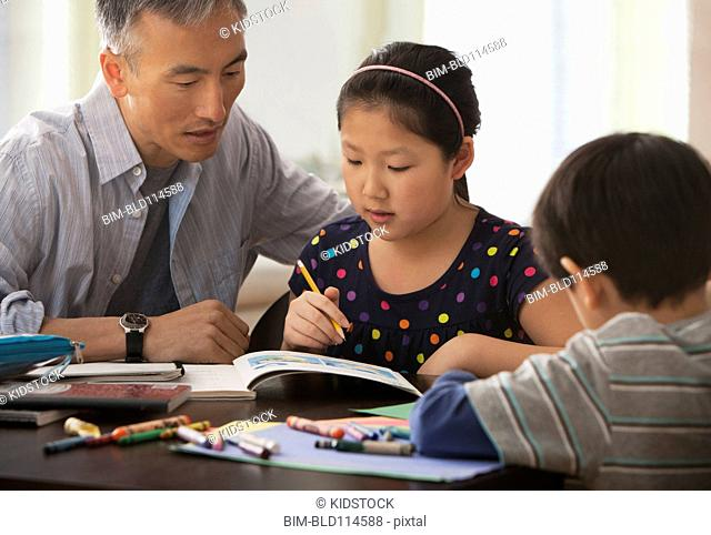 Father helping children do homework