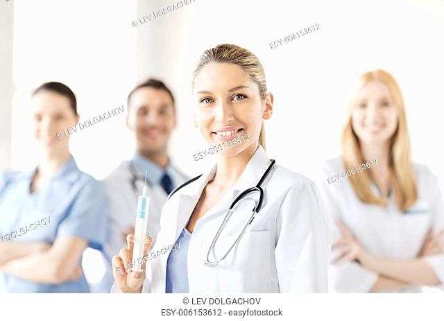 healthcare and medicine concept - group of medics with female doctor holding syringe with injection