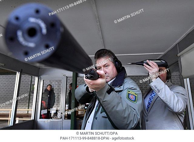 Ralf Brummel (L), head of the forestry department of ThuringenForst, holding a hunting firearm equipped with a suppressor during a demonstration in Suhl