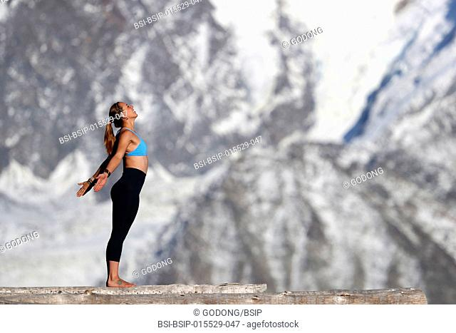 French Alps. Mont-Blanc massif. Woman doing yoga meditation on mountain. Saint-Gervais. France