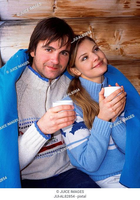 Couple wrapped in blanket with coffee