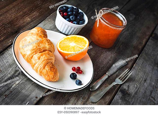 Fresh croissant, blueberries, orange and apricot jam on rustic wooden table. Angle view. Continental breakfast