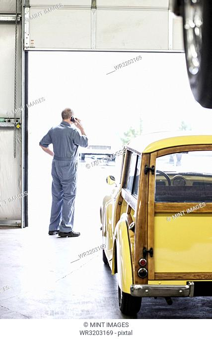 View from behind of an owner of a car repair shop on his cell phone
