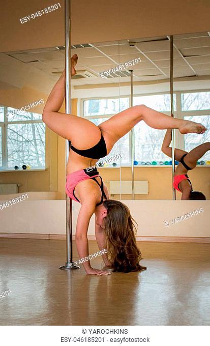 Pole dancer. a girl posing near pylon