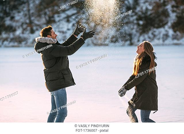 Side view of playful couple enjoying in snow