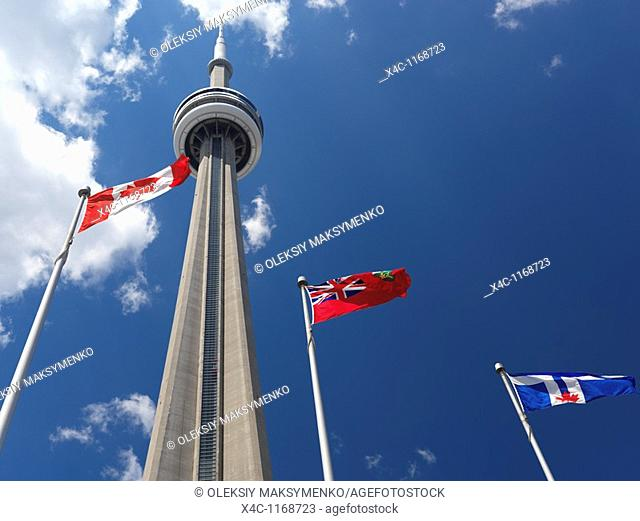 Toronto, Ontario and Canada flags flying in front of CN tower over blue sky