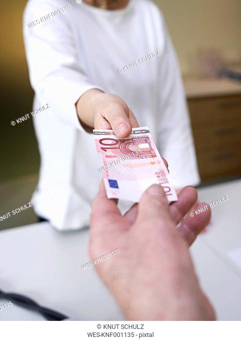Germany, Hamburg, Woman receiving cash from senior man, smiling