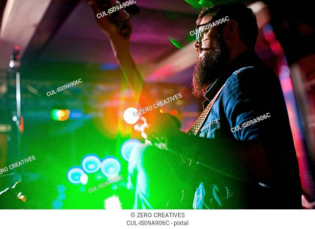 Man playing guitar in nightclub