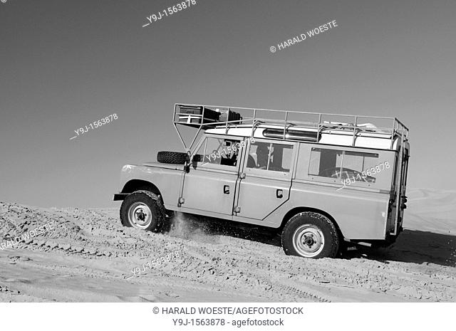 Africa, Tunisia, nr  Tembaine  Desert travellers driving their 1975 Land Rover Series 3 Station Wagon through a sandfield close to Tembaine on the eastern edge...