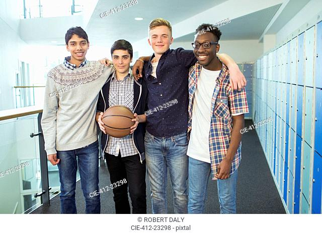 Group portrait of male students holding basketball in school corridor
