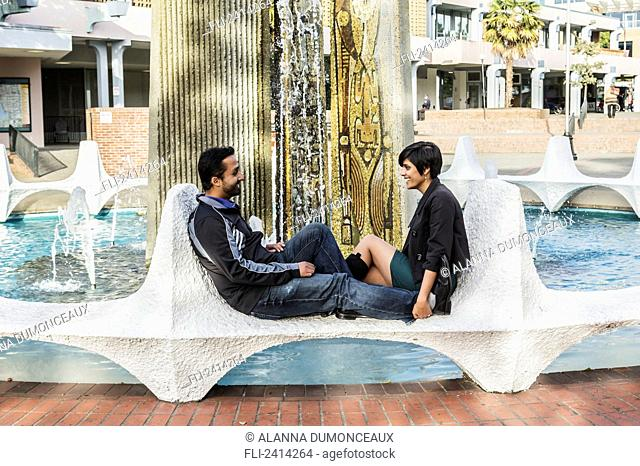 A young Indian ethnicity couple relaxing at the Ceramic Fins of Centennial Square fountain; Victoria, Vancouver Island, British Columbia
