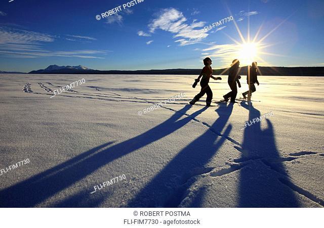 Snowshoers in bright winter sun on the frozen Teslin Lake, Yukon