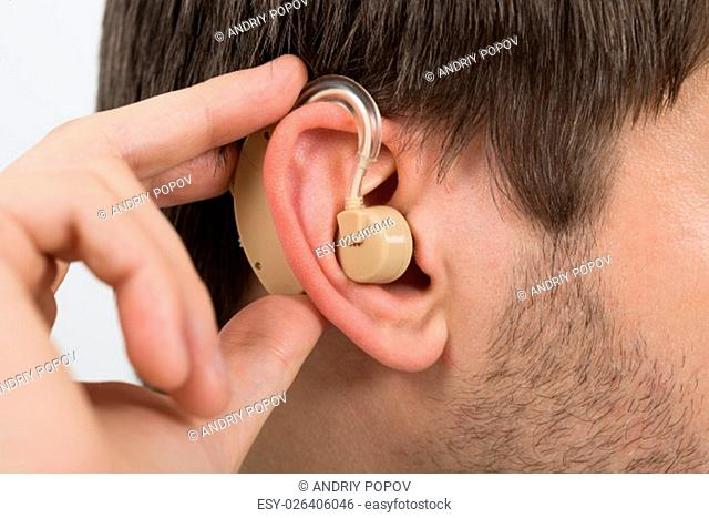 Close-up Of Man Wearing Hearing Aid In Ear