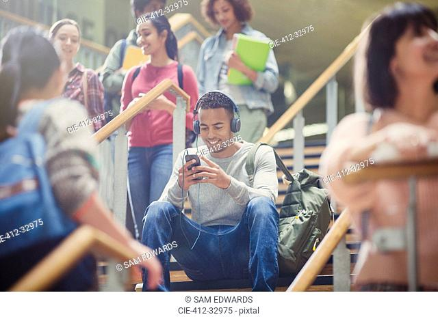 Male college student listening to mp3 player in busy stairway