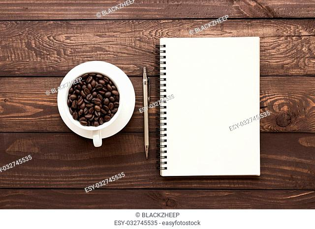coffee beans in cup and book blank page on wood table