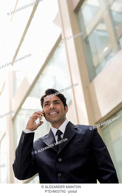 India, Businessman standing outside office building, talking on mobile phone
