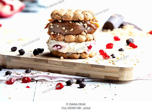 Stacked cookie with cream and caramel on chopping board, still life