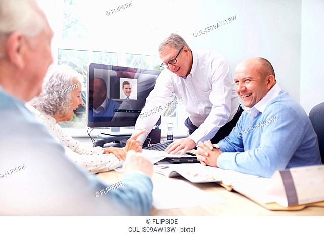 Business men in office having discussion with senior couple