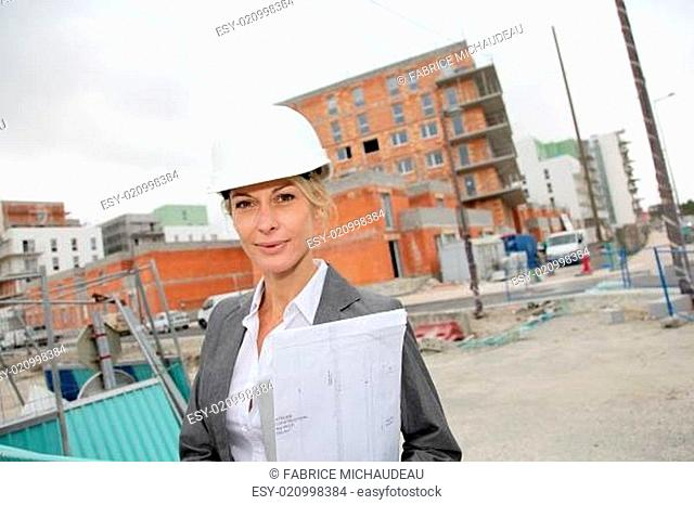 Woman engineer standing in front of building site