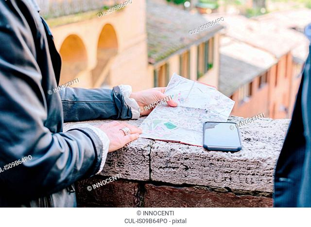 Cropped shot of tourist couple looking at map on wall, Siena, Tuscany, Italy