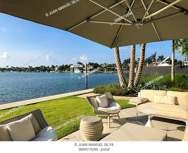 Patio furniture in backyard of house with water view, Key Biscayne, Florida, USA