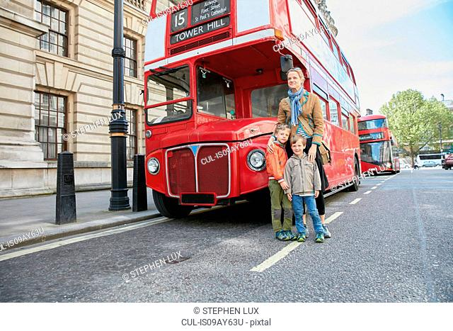 Mother and sons in front of red double decker bus