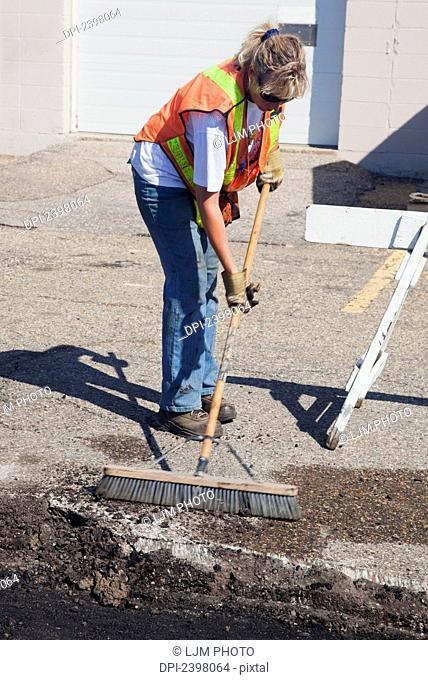Woman working to repair pot holes in parking lot; Edmonton, Alberta, Canada