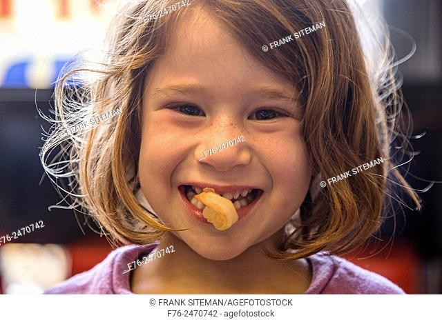 6 year old girl with a cooked shrimp in her mouth in a noodle restaurant in Berkeley, CA, USA