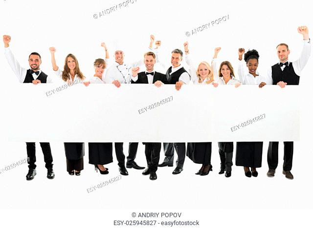Portrait of happy restaurant staff with arms raised holding blank billboard against white background