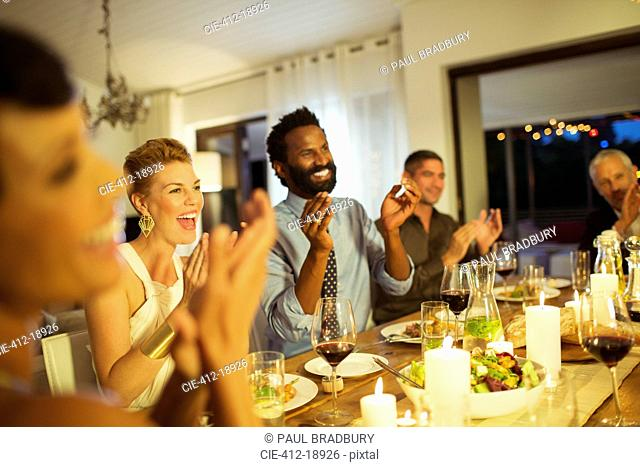 Friends cheering at dinner party