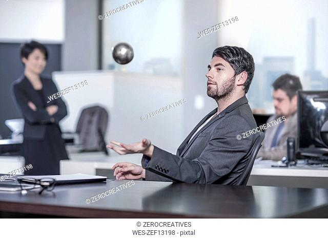 Man sitting at desk in city office throwing a ball in the air