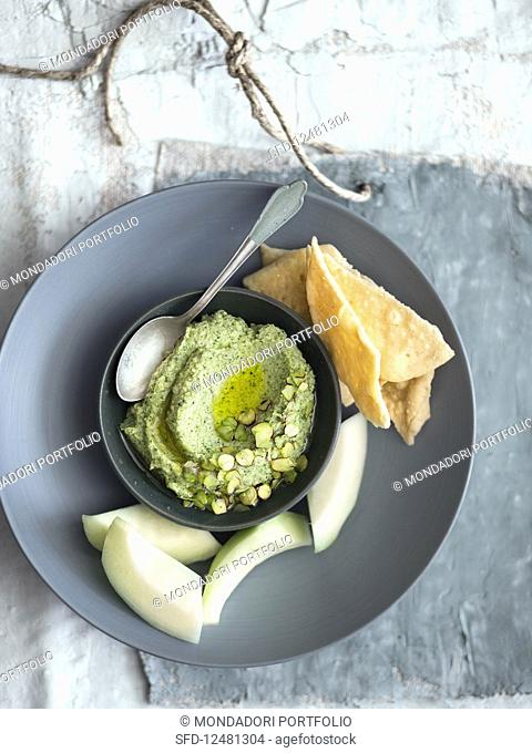 Dip made from grilled courgette, sheep's cheese and pistachios served with cucumber and schiacciatine
