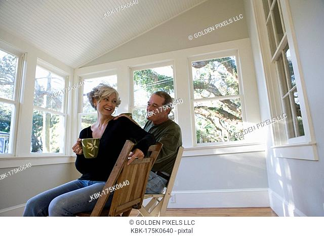 Portrait of mature couple sitting inside renovated house