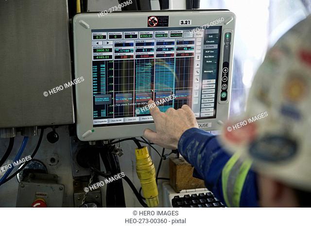 Engineer checking data computer monitor at gas plant