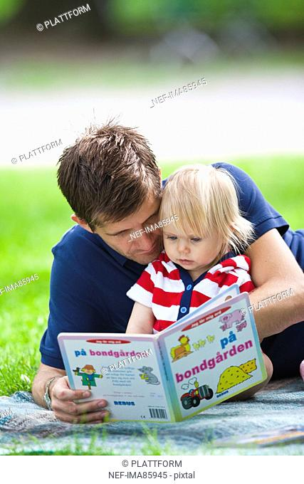 Mid adult father embracing daughter and reading her book