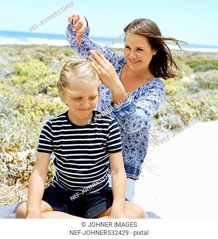 Scandinavian boy getting a haircut on the beach, Sweden