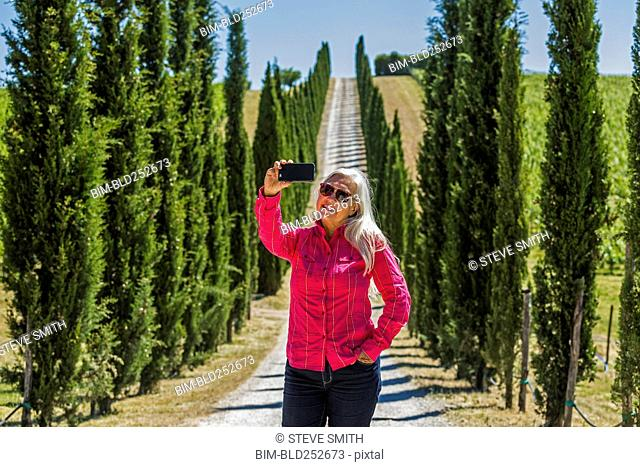 Caucasian woman posing for cell phone selfie on dirt road
