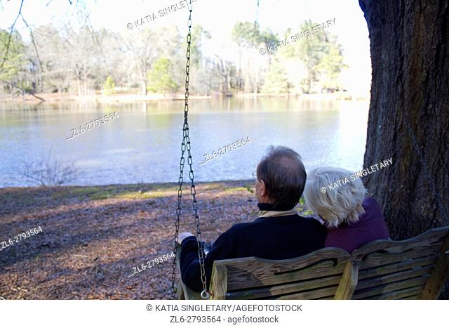 A caucasian couple in their 60's taking a walk around a lake a sitting on a swing, enjoying retirement