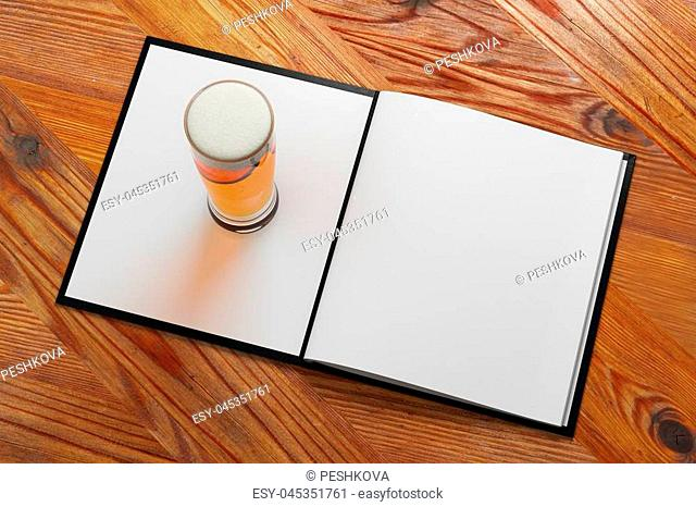 Top view of beer glass placed on empty white notepad. Wooden background. Menu, bar advert concept. Mock up, 3D Rendering