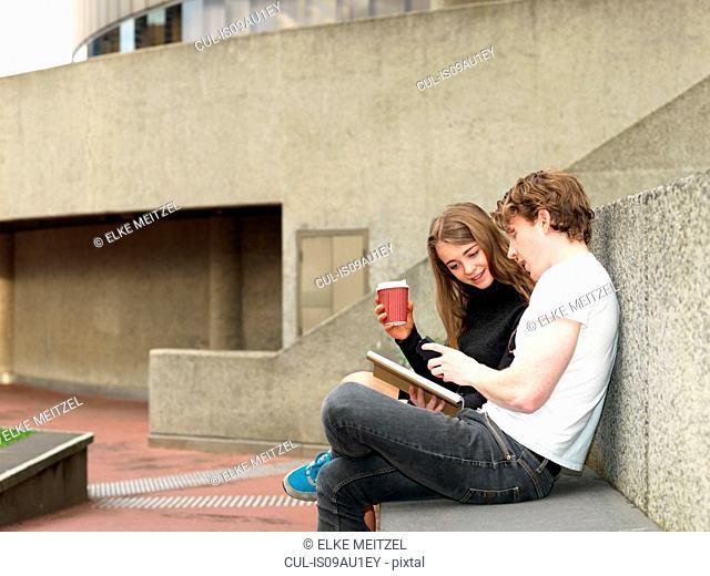 Young couple having coffee, using smartphone on concrete bench, Melbourne, Victoria, Australia