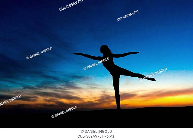 Silhouette of mid adult woman against dramatic sky, arms outstretched standing on one leg