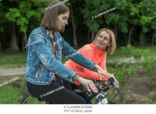 Smiling mother and daughter talking while riding bicycle at park
